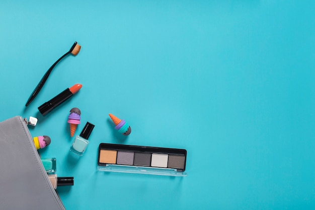 Flat lay of cosmetic accessories on blue background with copy space