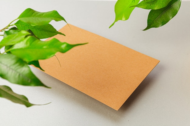 Flat lay craft paper card mockup with leaves, top view