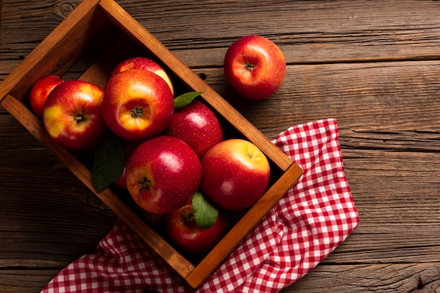 Flat-lay crate with ripe apples on cloth