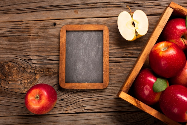 Flat-lay crate with ripe apples with blackboard