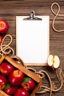 Flat-lay crate with ripe apples with clipboard
