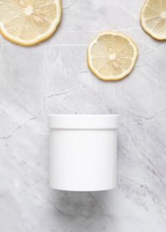 Flat lay of cream box and lemon slices on marble background