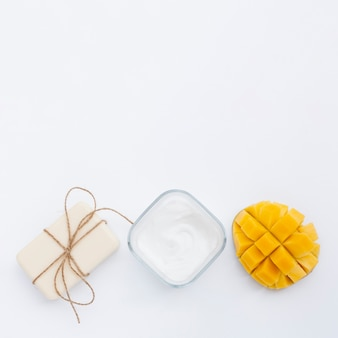 Flat lay of cream soap and mango with copy space