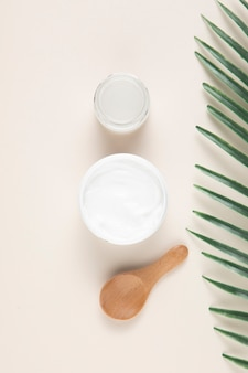 Flat lay of a cream and spoon on plain background