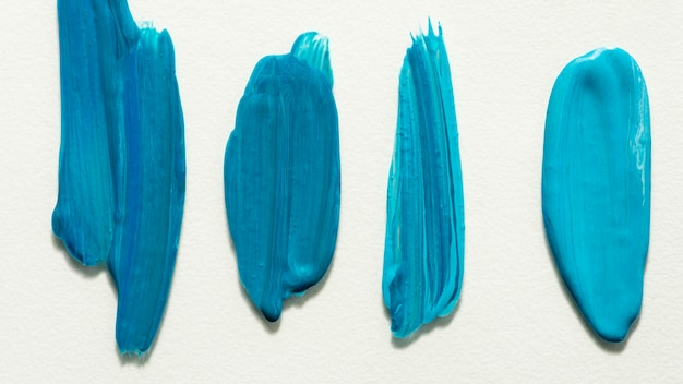 Flat lay of creative blue paint brush strokes on surface