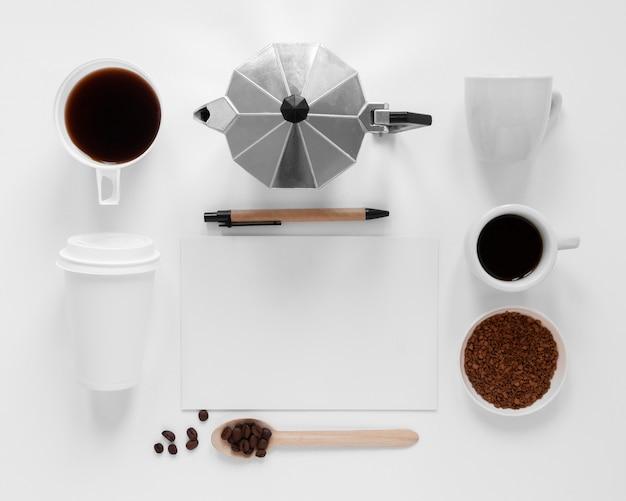 Composizione creativa laica piana degli elementi del caffè su fondo bianco