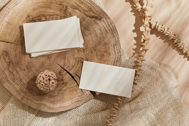 Flat lay of creative composition with mock up visit cards, textile, wood, natural materials, dry plants and personal accessories. neutral colors, top view, template.