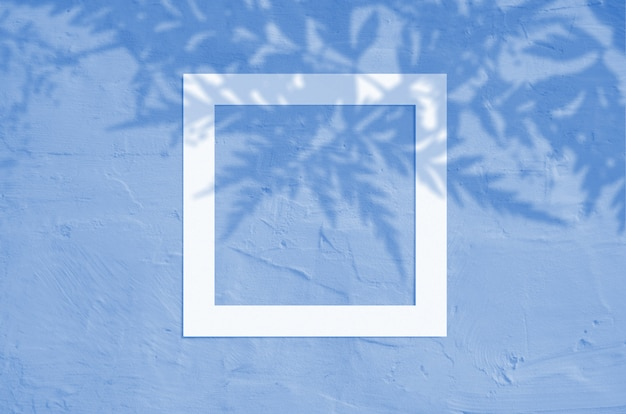 Flat lay of creative copyspace with paper frame and tropical leaves palm shadow. classic blue color. color of the year 2020.