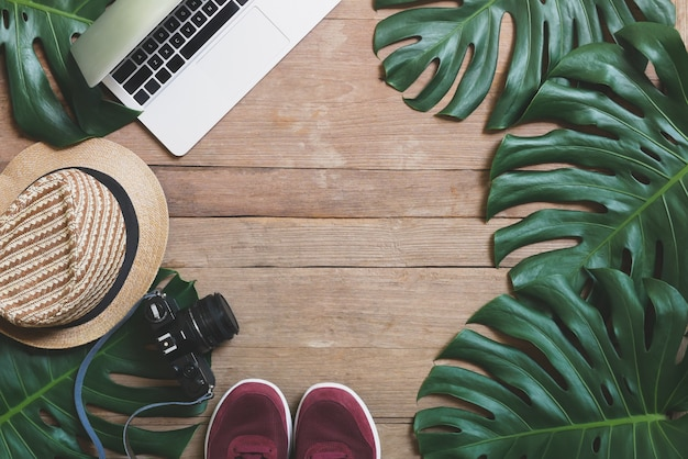 Flat lay creative frame of tropical nature leaves monstera on rustic wood grunge background with laptop computer, retro camera, hat and pair of sneaker shoes