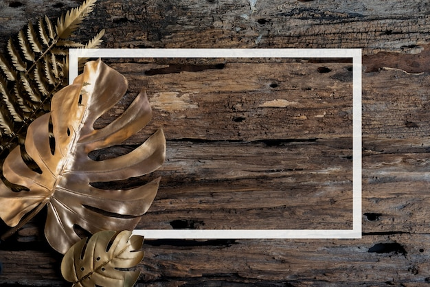 Flat lay creative frame of tropical nature leaves monstera on rustic wood grunge background with