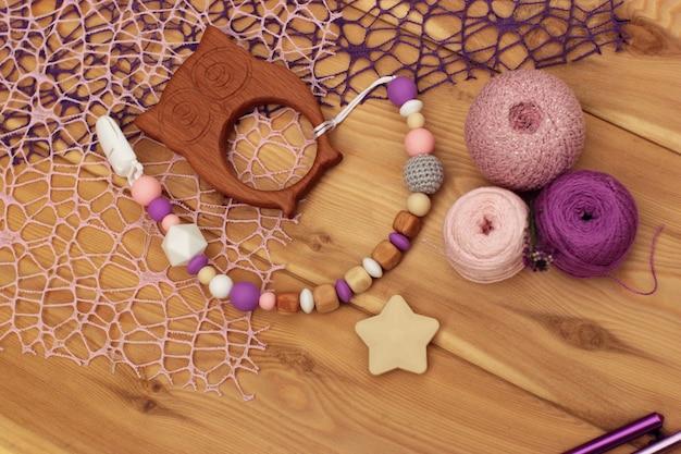 フラットレイかぎ針編みのベビーおしゃぶりホルダー。ヤーンボールとかぎ針編みのフック。