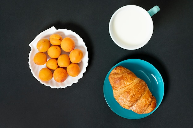 Flat lay croissant, milk and apricots on plain background