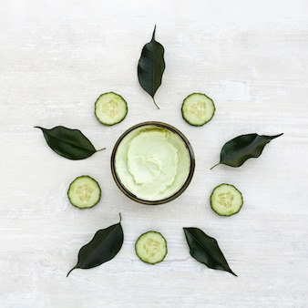 Flat lay of cucumbers and body butter on wooden table
