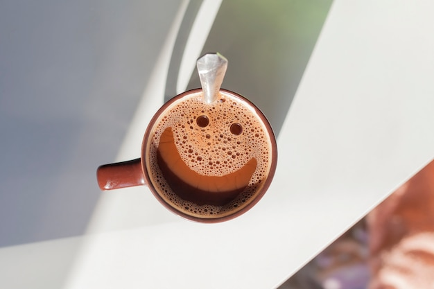 Flat lay cup of cocoa with a smiling bubble emoticon, sunny breakfast.