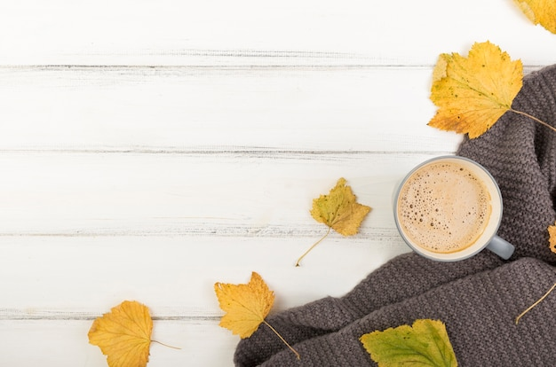 Flat lay cup of coffee and autumn leaves with copy space