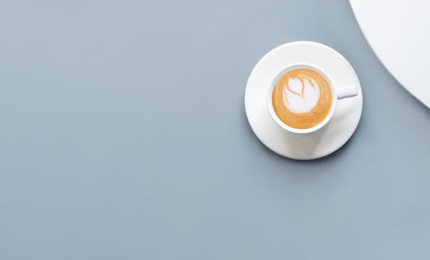 Flat lay cup of coffee cappuccino on blue background