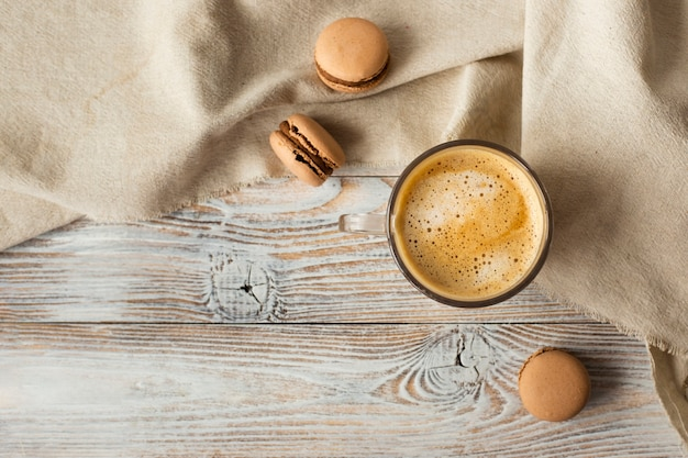 Flat lay of cup of coffee and macarons
