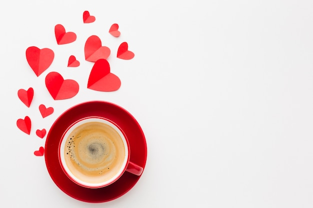 Flat lay of cup of coffee with valentines day paper heart shapes