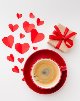 Flat lay of cup of coffee with valentines day present