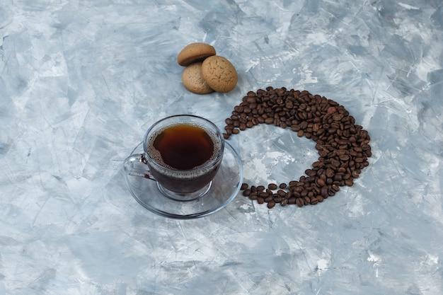 平らな一杯のコーヒー、水色の大理石の背景にコーヒー豆とクッキー。水平