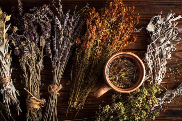 Плоская лежал чашка травяного чая с растениями