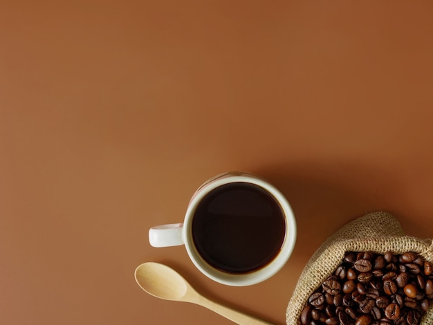 Flat lay a cup pf coffee on brown background with copy space