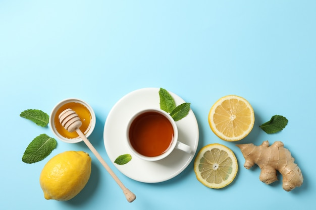 Flat lay. cup of tea, lemon, ginger, mint, honey and dipper on blue, copy space