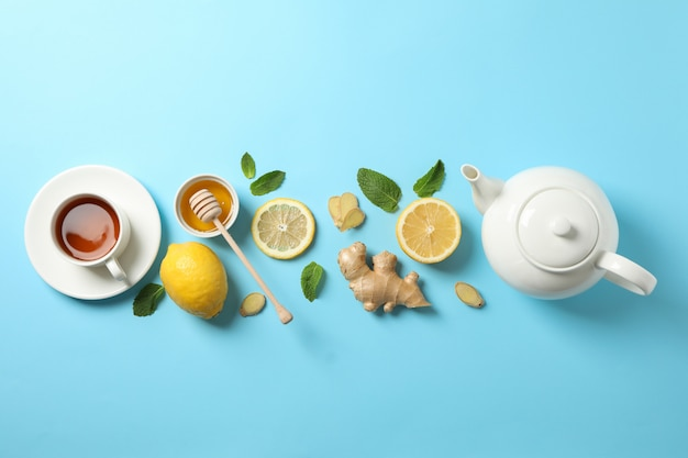 Flat lay. cup of tea, teapot, lemon, ginger, mint, honey and dipper on blue, copy space