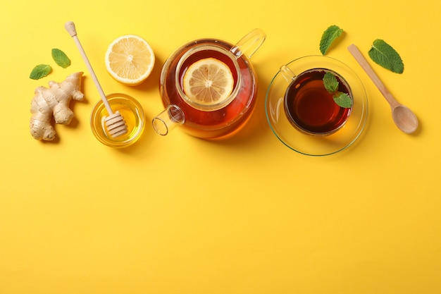 Flat lay. cup of tea, teapot, lemon, ginger, mint, honey and dipper on yellow, copy space