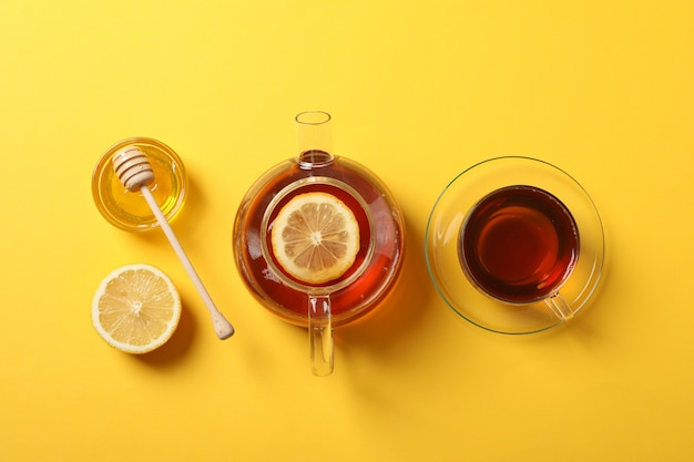 Flat lay. cup of tea, teapot, lemon, honey and dipper on yellow, copy space