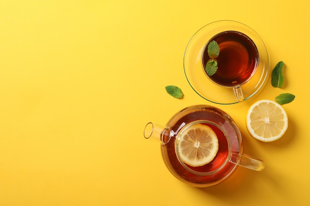 Flat lay. cup of tea, teapot, lemon and mint on yellow, copy space