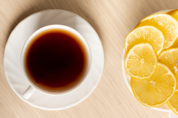 Flat lay cup of tea with lemon arrangement on plain background