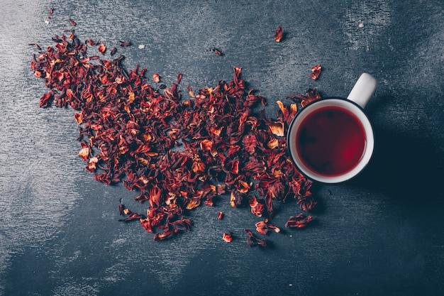 Piatto giaceva una tazza di tè con erbe aromatiche su sfondo scuro con texture. orizzontale