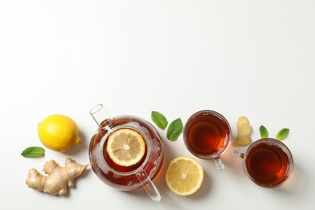 Flat lay. cups with tea and teapot, lemon, mint and ginger, space for text