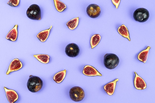 Flat lay of cut and whole figs on a blue background. copy space.