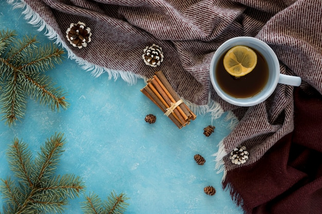 Flat lay cute winter hot cup of coffee on scarf