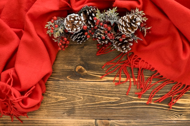 Flat lay cute winter pine cones on red scarf