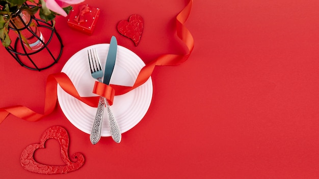 Flat lay of cutlery on plate with ribbon and hearts