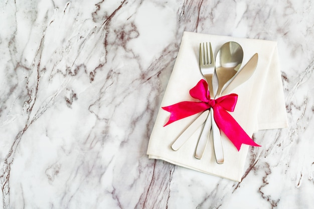 Flat lay - cutlery, spoon fork and knife on a rustic napkin and a bow of silk ribbon lie on a marble table background