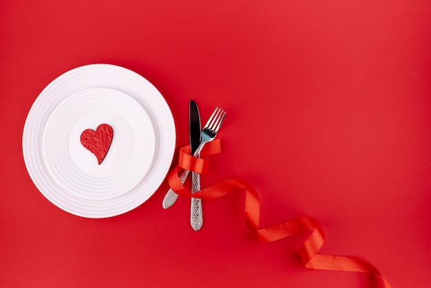 Flat lay of cutlery with heart on plate and copy space