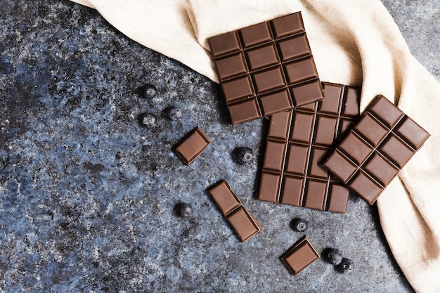 Flat lay dark chocolate on cloth with blueberries