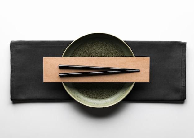 Flat lay of dark dinnerware with chopsticks and napkin