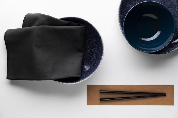 Flat lay of dark dinnerware with chopsticks