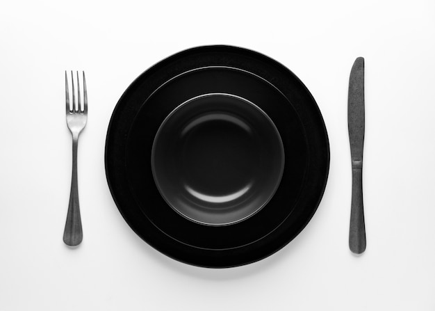 Flat lay of dark dinnerware with cutlery