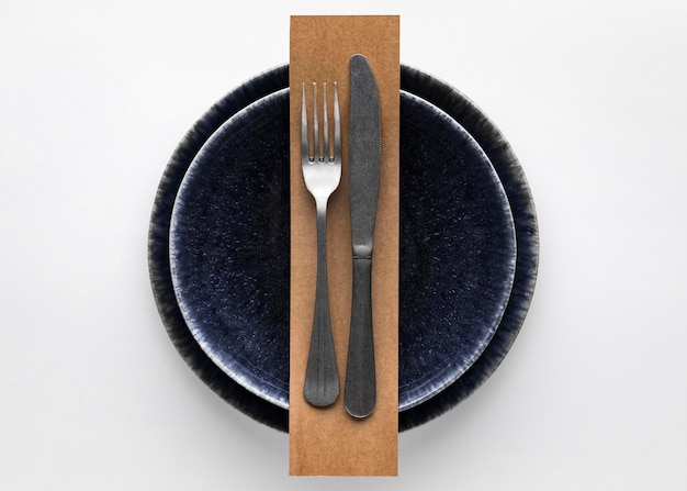Flat lay of dark dinnerware with  fork and knife