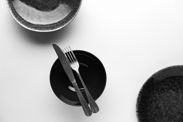 Flat lay of dark dinnerware with knife and fork