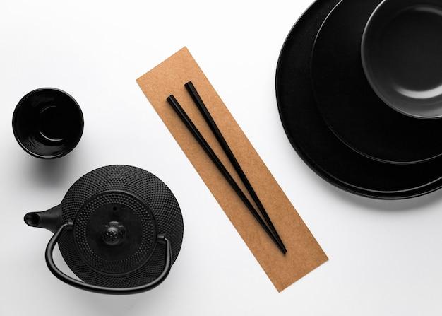Flat lay of dark dinnerware with teapot