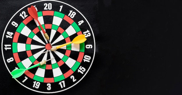 Flat lay darts table on black background with copy space