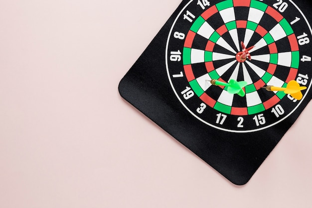 Flat lay darts table on pink background with copy space
