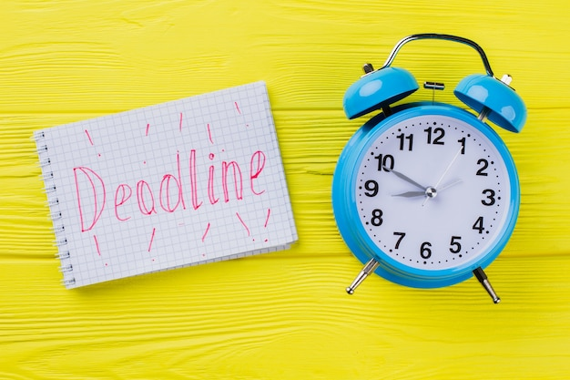 Концепция крайнего срока плоской планировки. синий будильник с блокнотом со словом крайний срок на желтой древесине.
